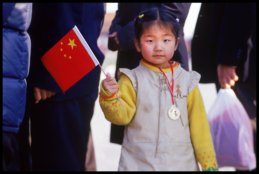 A young girl in line with her parents to see Mao's tomb in Tienanmen Square.