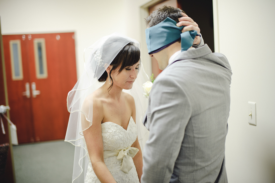 couple prayes before wedding ceremony with blindfold