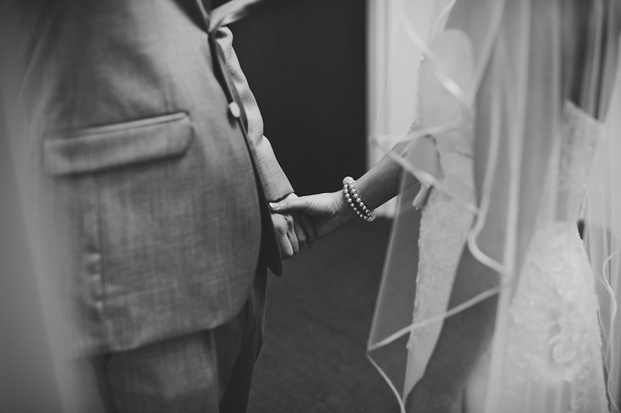 couple holding hands before wedding ceremony with blindfold