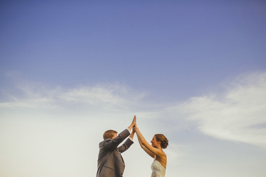 bride and groom jump, high five