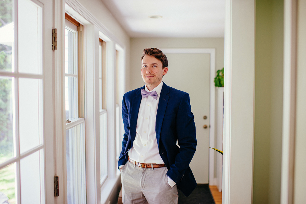 wedding groom blue jacket, grey slacks, purple bow tie