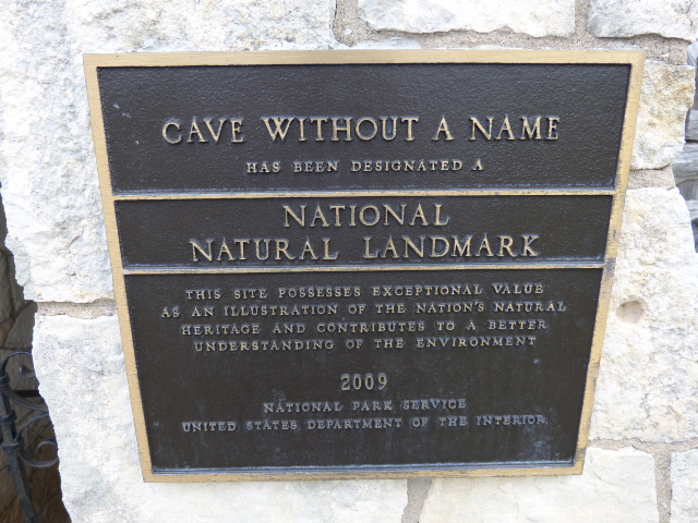 Plaque by the gate that guards the cave entrance and the 85 steps down