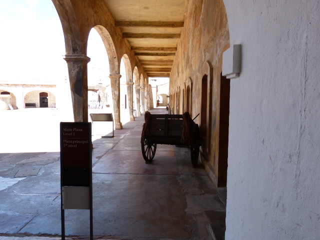An arched shaded walkway on the main plaza. There are three levels to the Castillo.