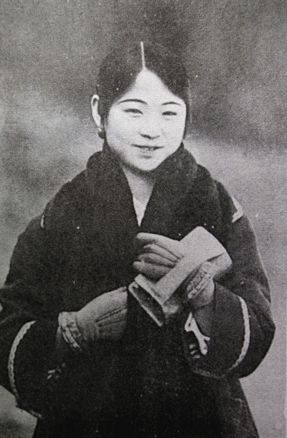 A gisaeng girl wearing Western coat, gloves, and a fur scarf holding a little clutch.