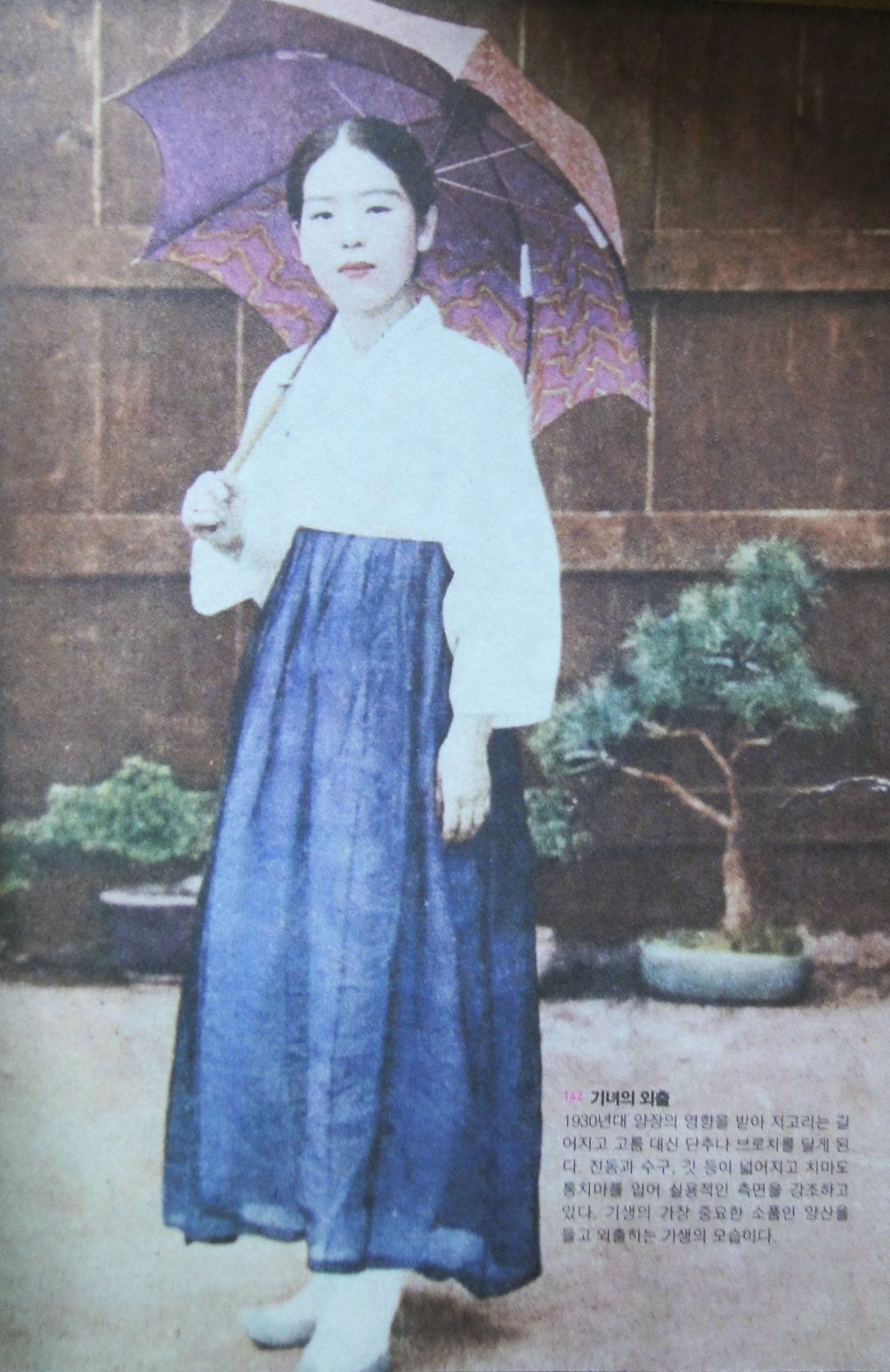 A gisaeng girl ready for going out. The fastening of the top is Westernised - from tying up to buttons. The sun umbrella was a symbol of gisaengs back then.