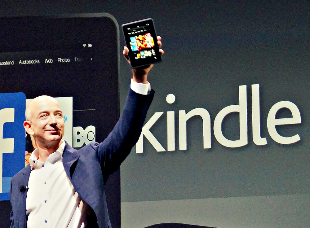 Jeff Bezos holding up a Kindle.