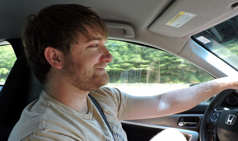 Josh drapes his arm casually over the steering wheel as he heads towards our first destination--Lonesome Lake.