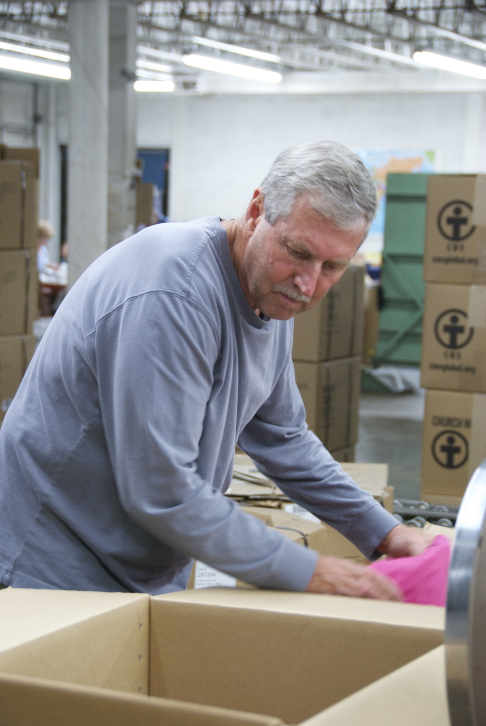 Dan Namet helps by packing boxes on a Church World Service mission trip