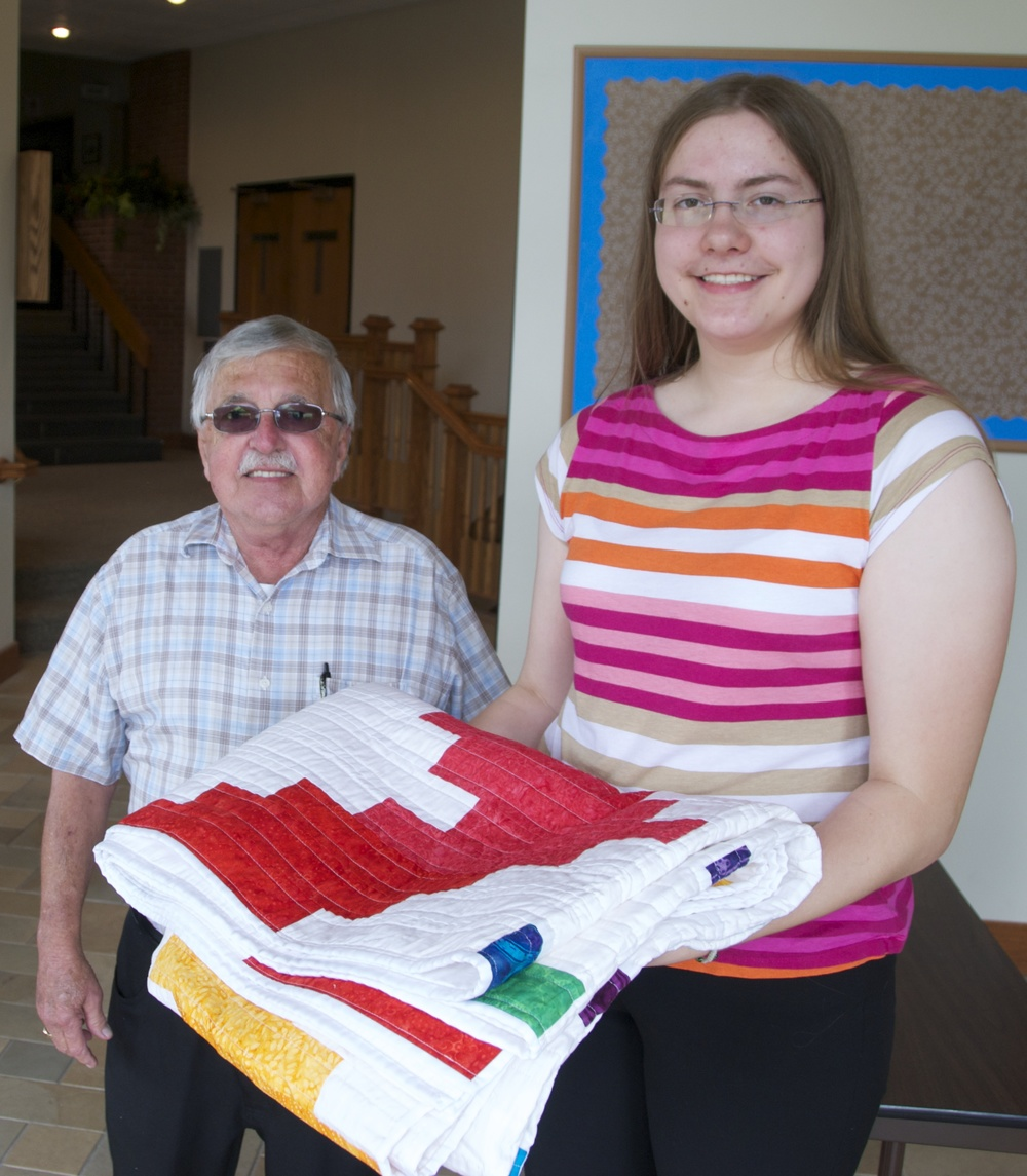 Kate Plajer presents James Kaufman with a quilt that benefitted Our Church's Wider Mission