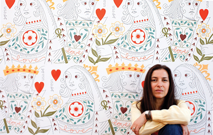 Portrait of Jeanne Greco, photographed by Jean-Luc Fievet, in front of a wall enlargement of the 2009 USPS Love Stamp, The King and Queen of Hearts.
