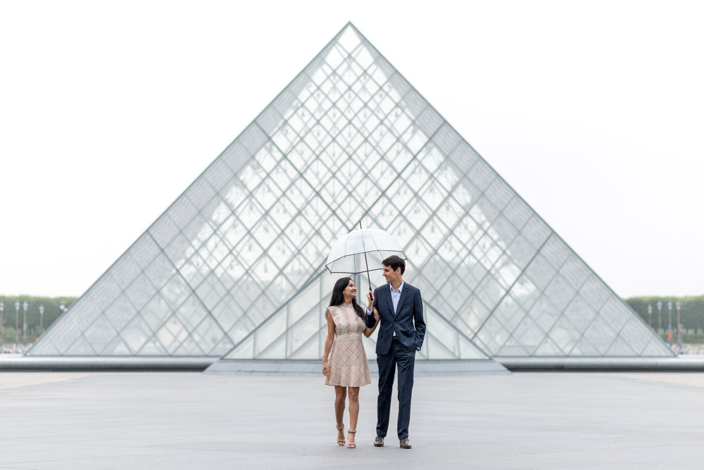 Paris-photographer-Paris-for-Two-Christian-Perona-professional-engagement-proposal-pre-wedding-portrait-Louvre-Museum-sunrise-rain-rainy-day-umbrella-side-by-side.jpg