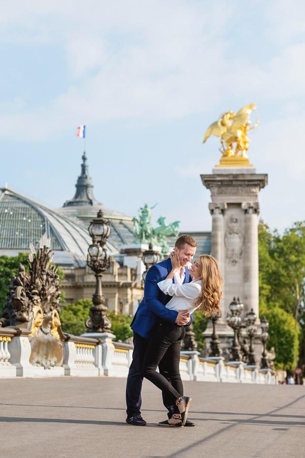 paris-photographer-christian-perona-professional-engagement-proposal-pre-wedding-portrait-Alexandre-III-bridge-pont-golden-statue-grand-palais-smiling.jpg