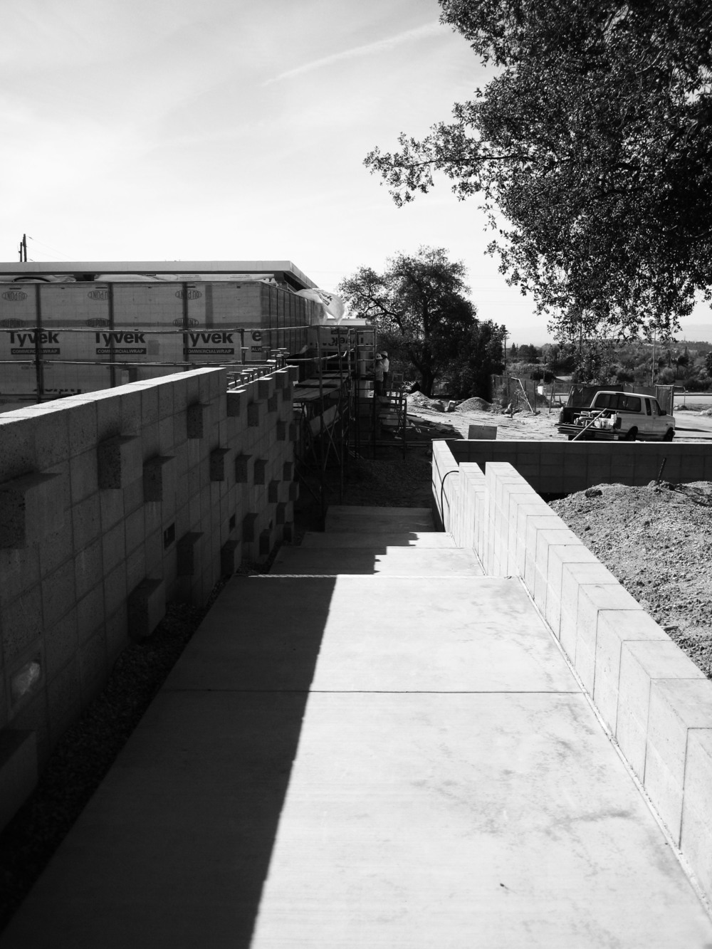 An articulated concrete block wall greets visitors approaching from the parking area.  Landscaping and lighting have also since been installed in the planter to the right.