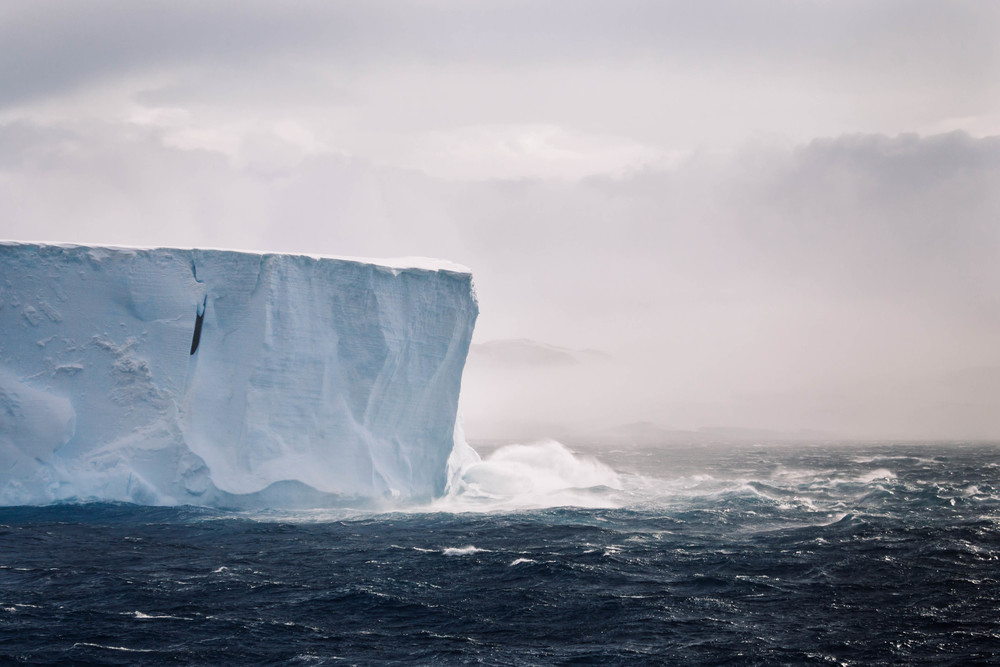 A dramatic tabular iceberg takes a wave as we pass through the Antarctic Sound.