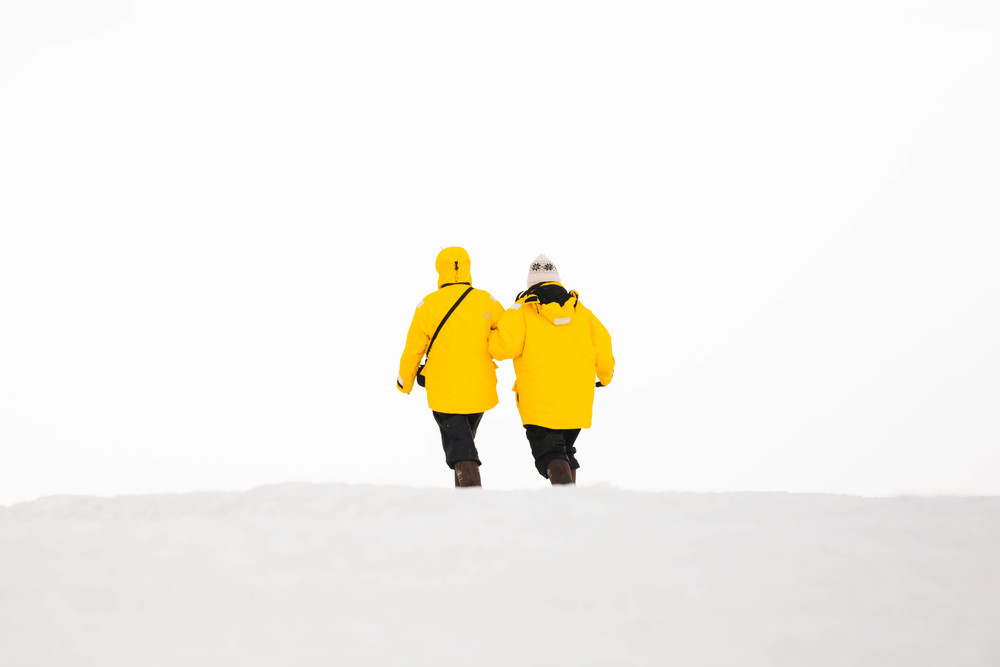 Passengers walking on shore wearing signature, bright yellow Quark parkas.