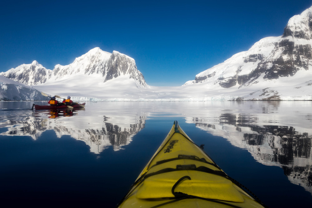 Mirror waters and epic peaks as we paddle along near Jougla Point and Goudier Island.
