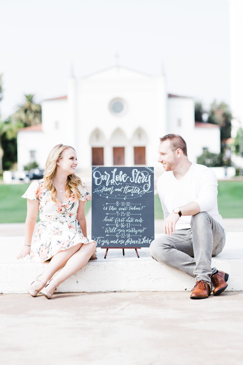The sign gives context as to why they are not close together. With space, they are now free to make eye contact with each other as the context of the portrait becomes their connection to each other and the important dates leading up to their wedding.