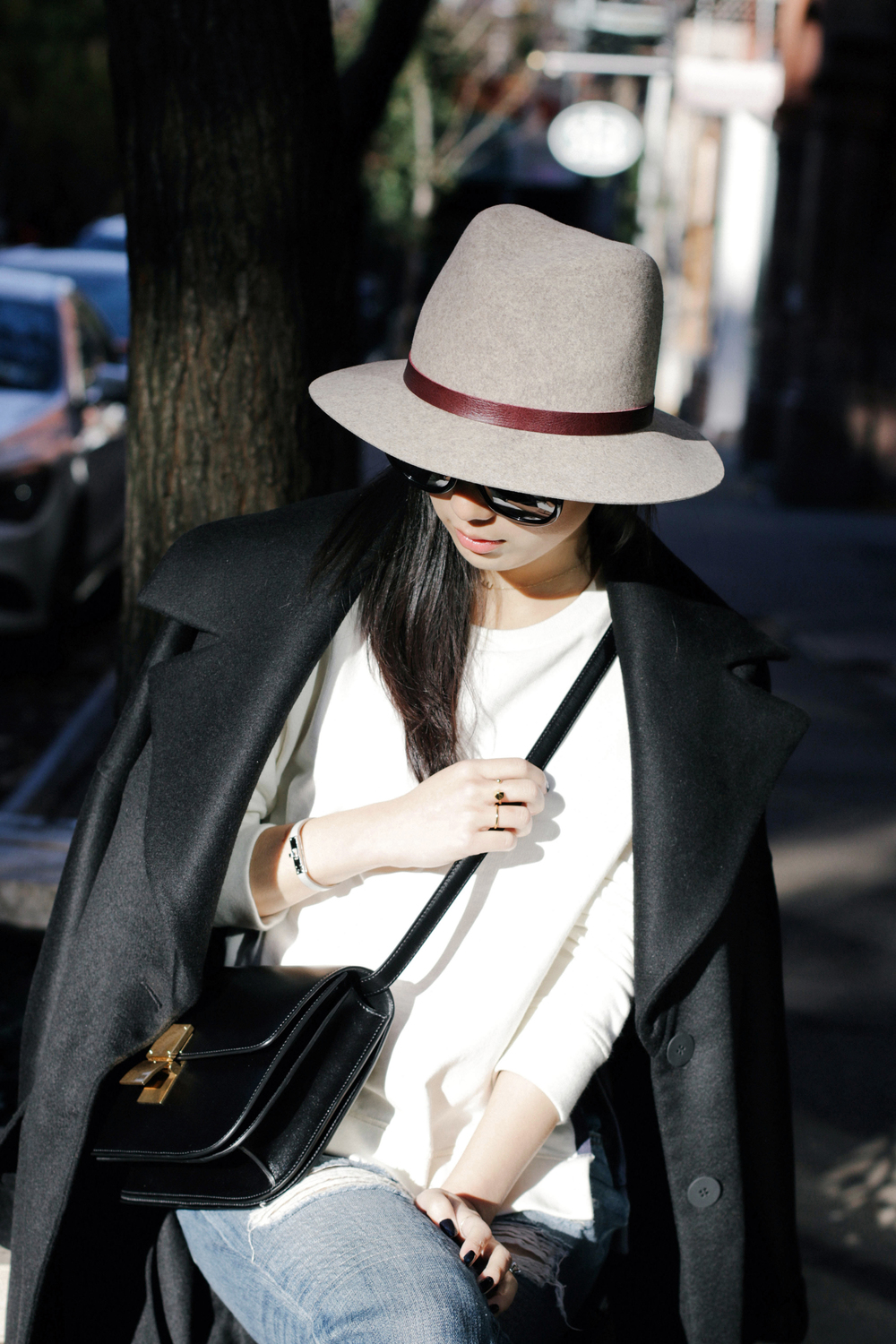 Michelle Waugh Coat, Acne Studios Top, Rag & Bone Jeans, Camilla Skovgaard Boots, Céline Bag, Janessa Leone Hat, The Row Sunglasses (Tortoiseshell), Hermes Bracelet (Black), Brandy Pham Rings (One, Two)