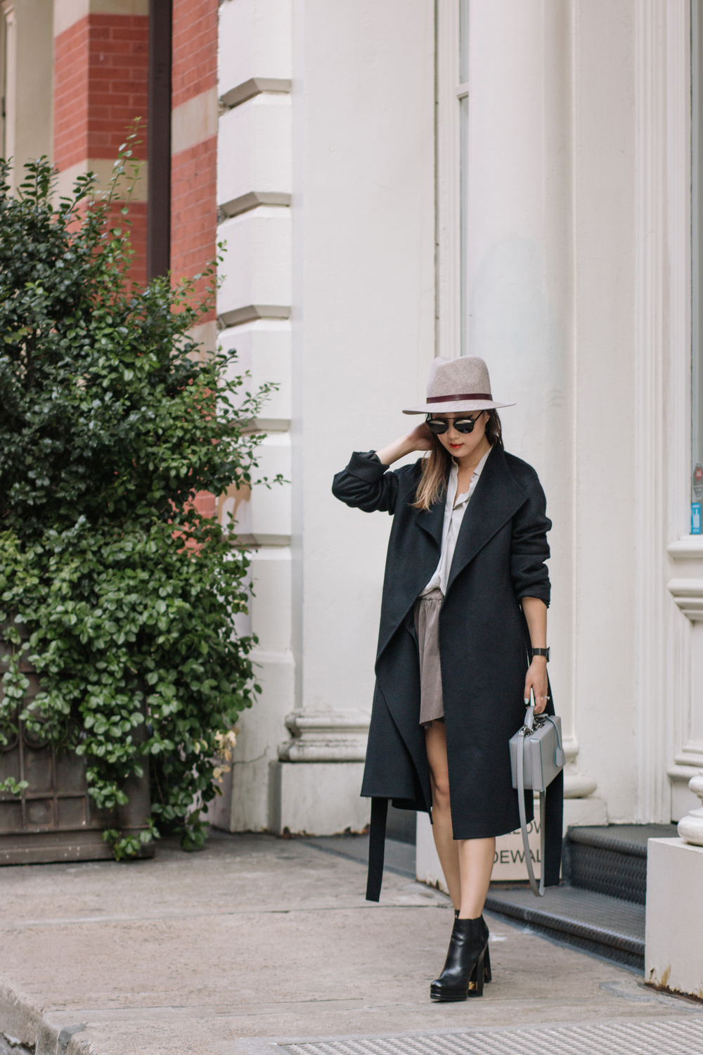 Kuho  Coat,  Everlane Shirt ,  Aritzia Skirt , Chanel Shoes,  Janessa Leone Hat ,  Mark Cross Bag ,  Dior Sunglasses ,  Larsson & Jennings Watch