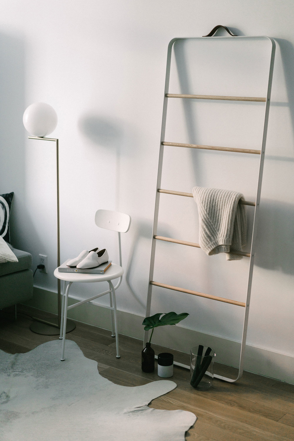 At home – Flos Lamp, Menu Chair and Ladder, The Row Shoes, Nili Lotan Sweater
