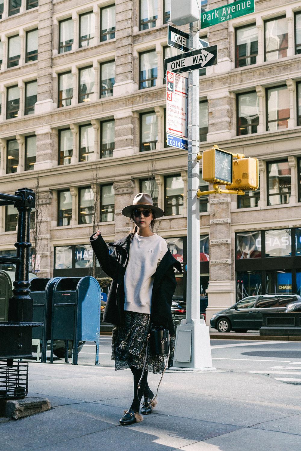 Michelle Waugh Coat, Acne Studios Sweatshirt, Chloé Skirt, Gucci Shoes, Cafune Bag, Janessa Leone Hat