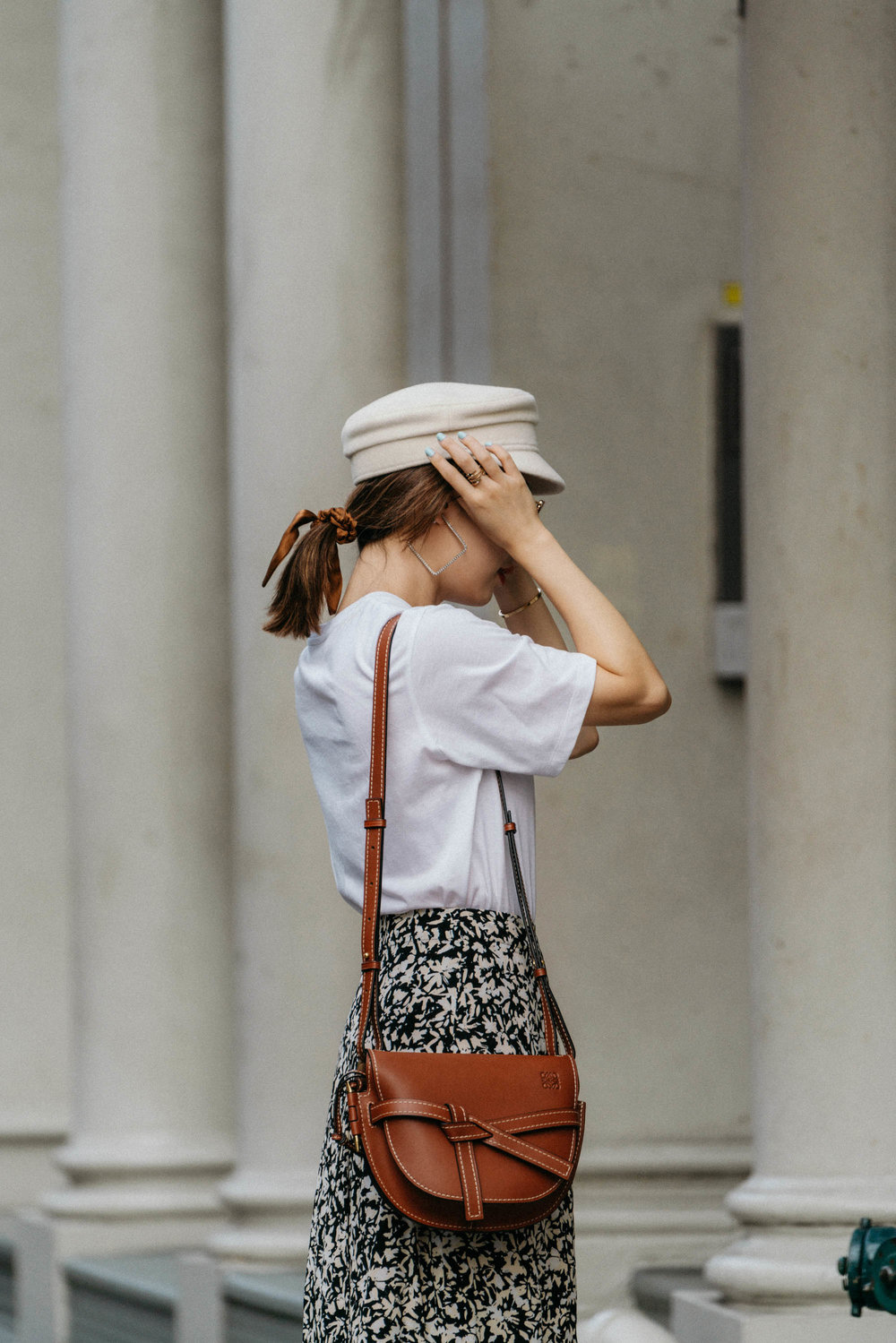 Common Odds Shirt,  Proenza Schouler Skirt,  Loewe Bag ,  Ruslan Baginskiy Hat ,  Donni Scrunchie ,  AREA Earrings