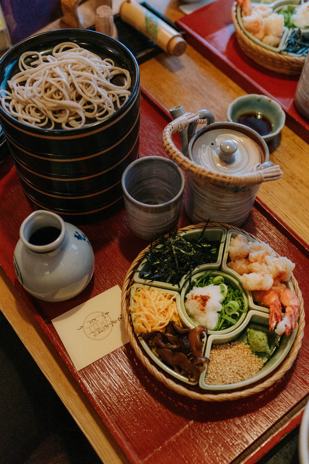 Cold Hourai soba that comes with 8 toppings of shiitake mushrooms, shredded omelet, shrimp tempura, nori, wasabi, grated daikon, sesame seeds, and green Japanese leeks