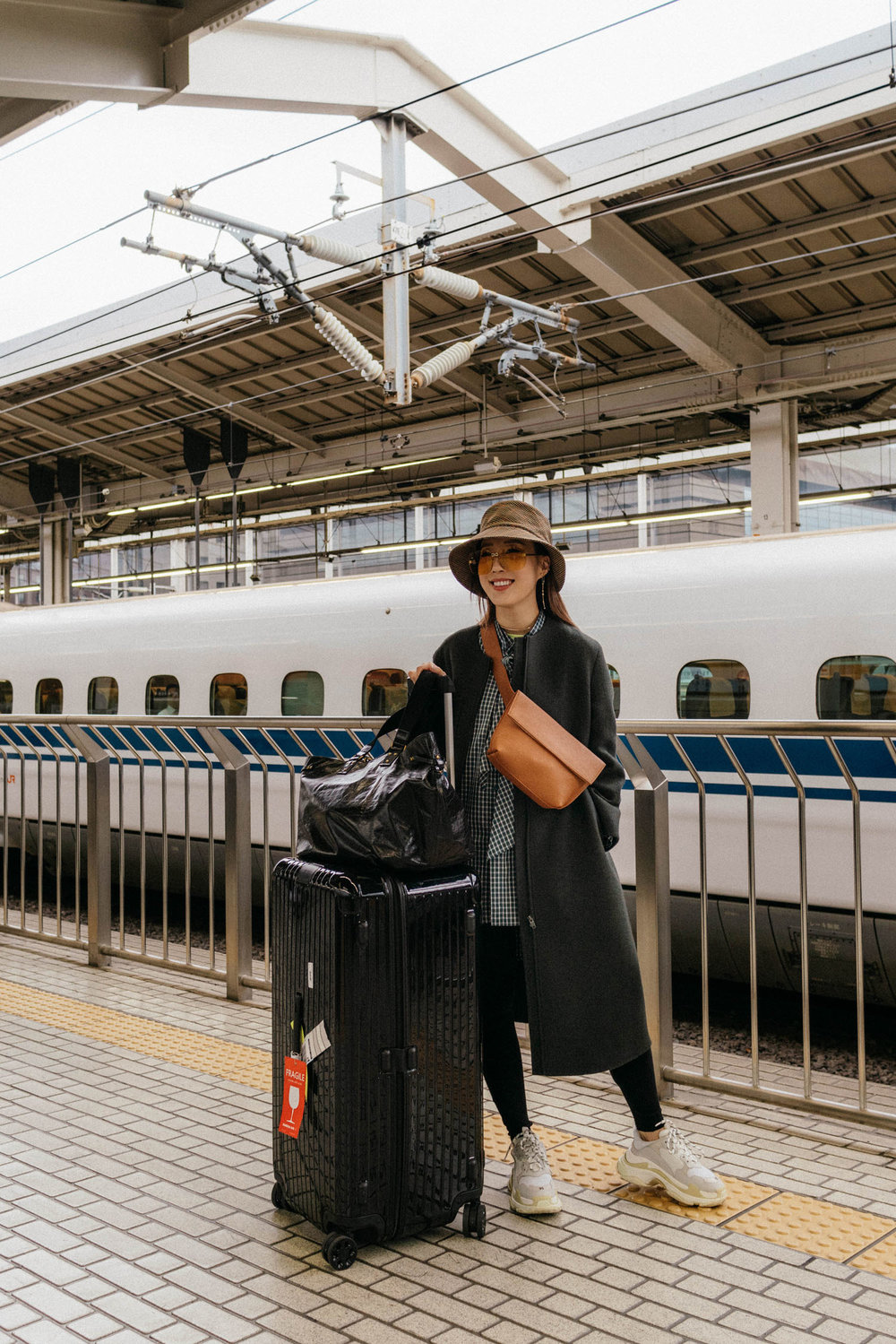 Kuho Coat , Balenciaga Top,  Alexander Wang x Uniqlo Leggings ,  Balenciaga Sneakers ,  Yvonne Kone Bag ,  Eric Javits Hat ,  Isabel Marant Bag ,  Rimowa Luggage