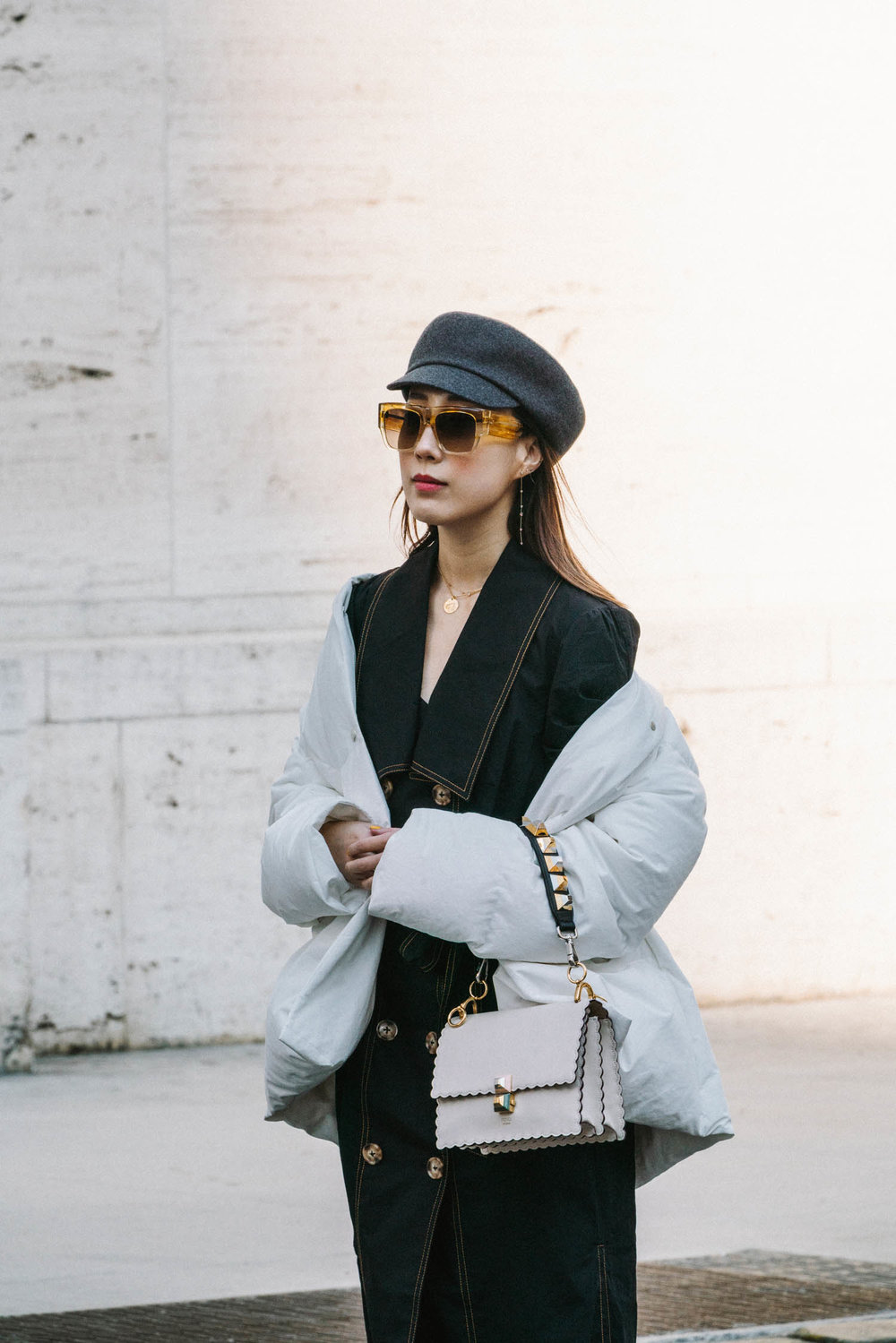 Jil Sander Coat ,  C/meo Collective Dress ,  Fendi Bag ,  Comme des Garçons Shoes , Hermes Hat,  Celine Sunglasses ,  WWAKE Earrings ,  Louis Vuitton Necklace
