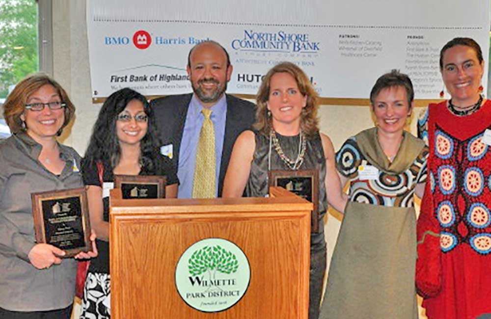 (2011 - 2012)   Winnetka Is Neighborly wins the 2012 Rayna & Marvin Miller Housing Justice Award from Open Communities. In addition to the Property Maintenance Code victory for renters, WIN also helped gain passage of a coach house ordinance, allowing 30 homeowners to turn their coach houses into rentals if they so choose. Left to right: Nancy Pred, Surrosh Shakir, Mark Miller (presenting the award), Ann Airey, Katie Seigenthaler, and Jen McQuet.