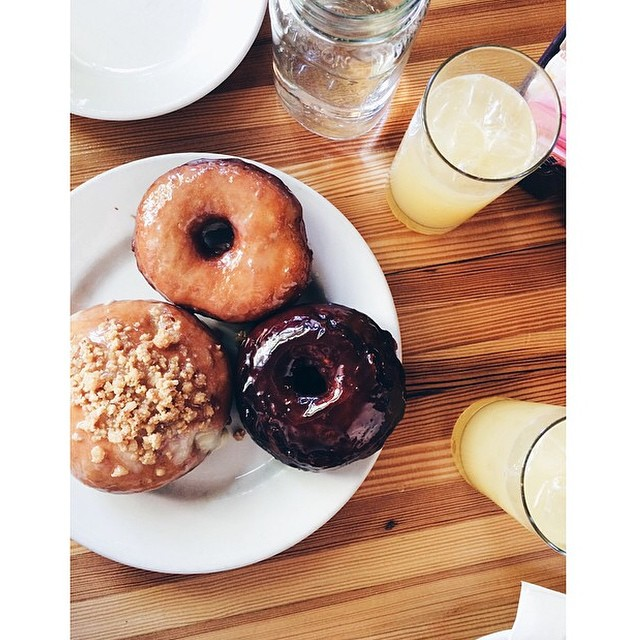 Assorted donuts featuring Chipotle chocolate, apple cider glaze, banana creme filling with bacon peanut butter brittle. You heard right! Brunch starts at noon! Beautiful #regram from @katiebasss