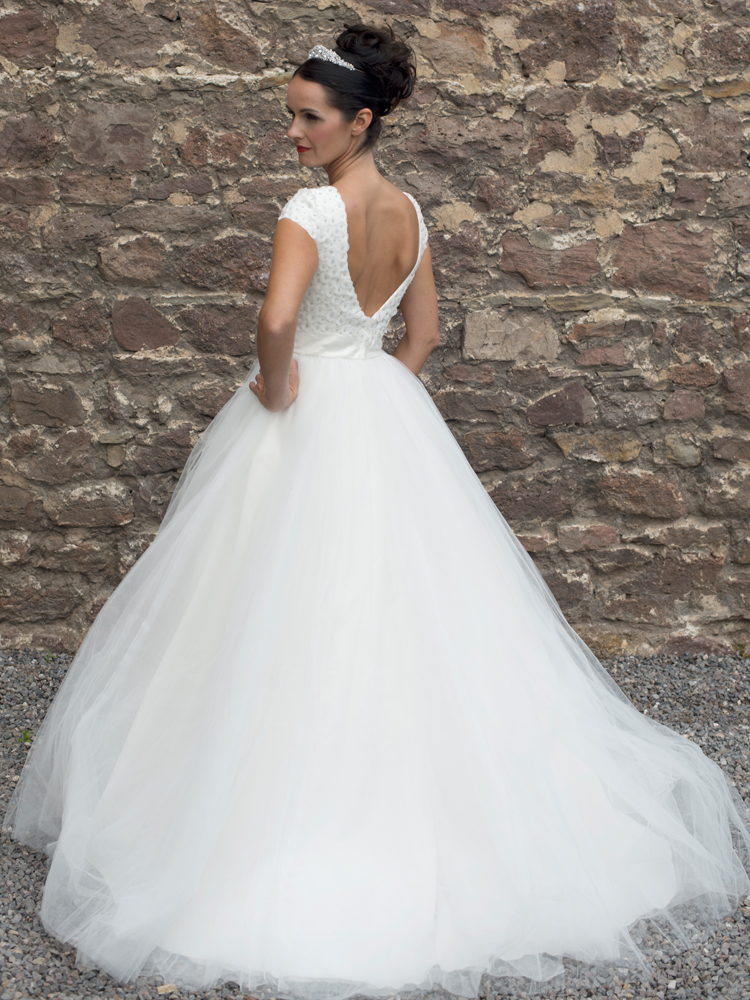A full skirt with layers of English net provides perfect contrast to the stunning crystal-embellished, cap-sleeved bodice with deep V back detail.
