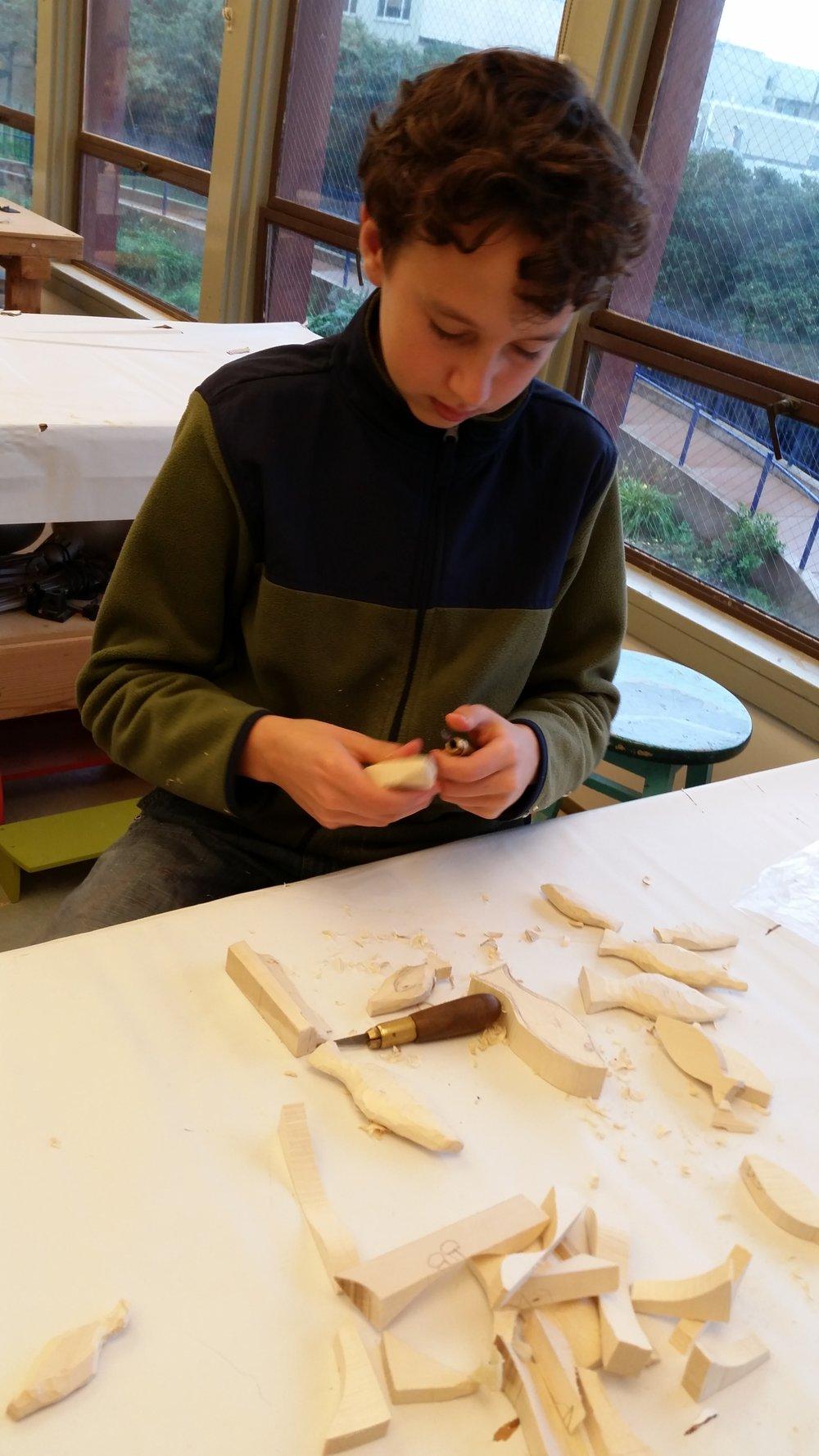 Tim is carving fish for a fish rattle.  Knife work is a more advanced skill and he is handling it like a pro.