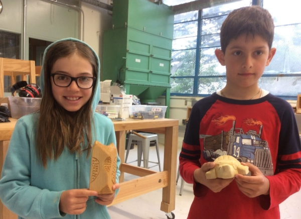 Two of the young carvers from the Randall class show off their newly completed owl and turtle sculptures.