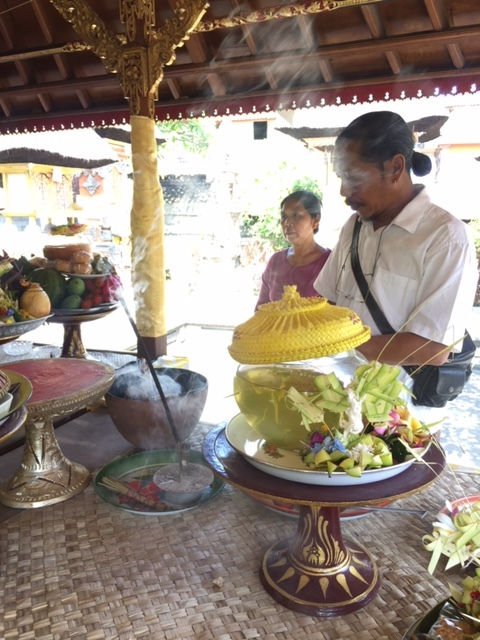The alter is covered with elaborate floral arrangements and luscious fruit and rice offerings.