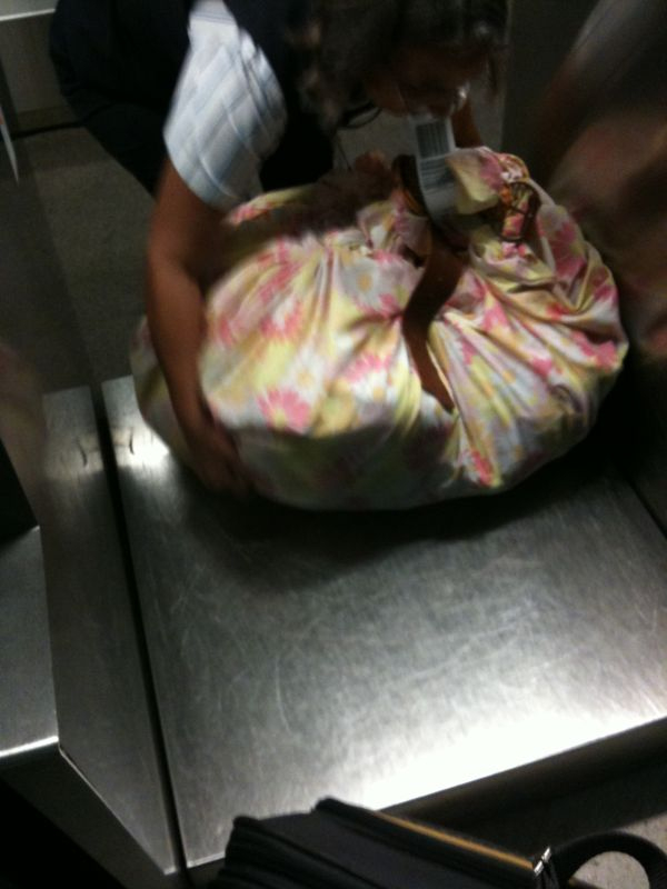 This ladies bag she checked was essentially a bed sheet tied & closed with a belt..