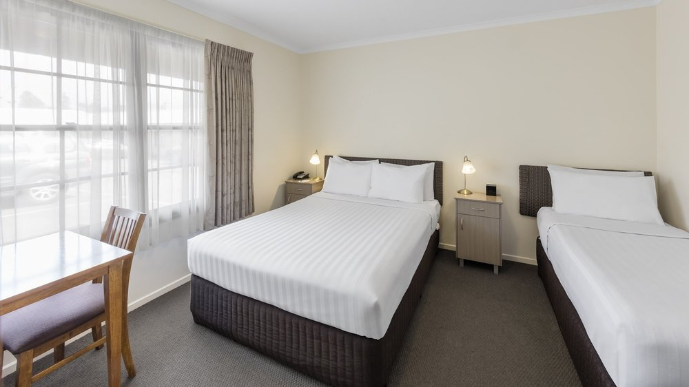 Standard Twin - A renovated motel style room with 1 x queen bed & 1 x single bed, and a private ensuite bathroom.⨠ View Room Details