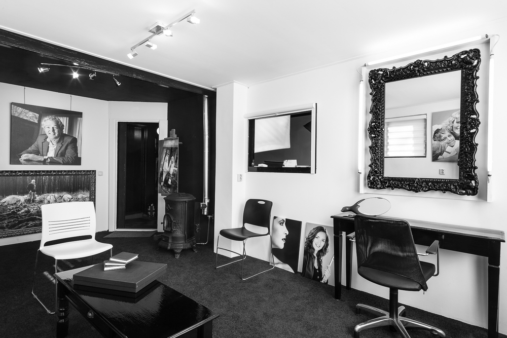Ontvangst ruimte met koffiecorner, kledingrek, kappersstoel, visagiekruk en goed verlichtte spiegel.