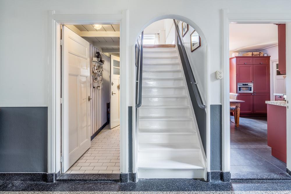 Zicht vanuit de woonkamer op toegang toilet, trapopgang en keuken
