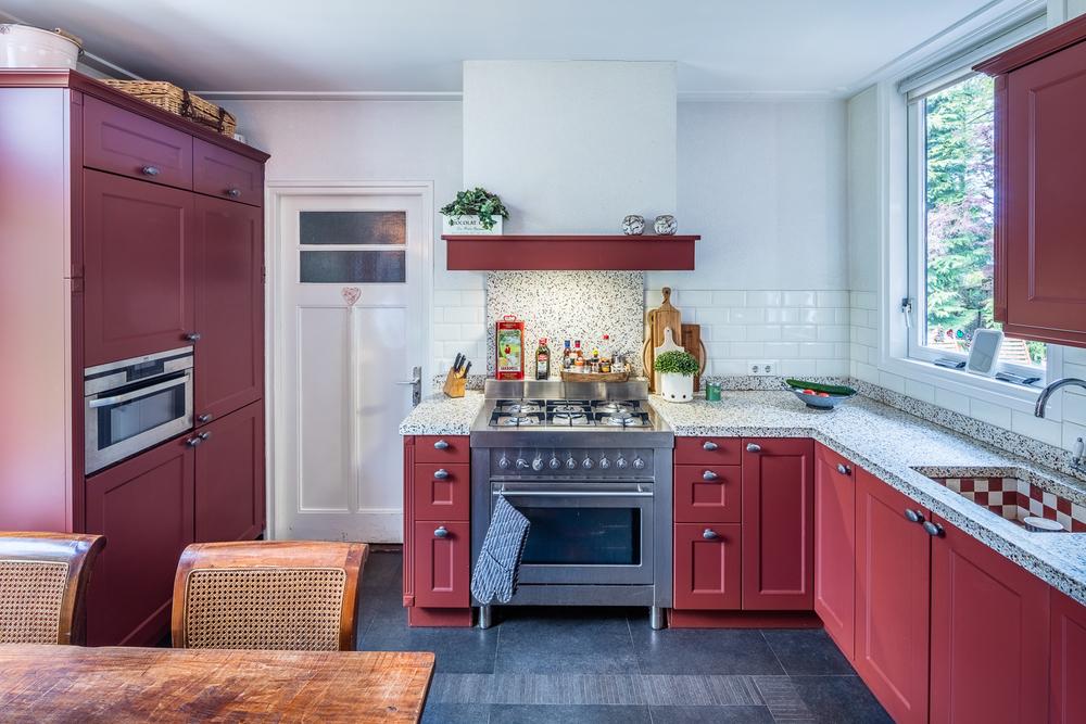 Keuken met doorgang naar bijkeuken en zicht op de achteringang.