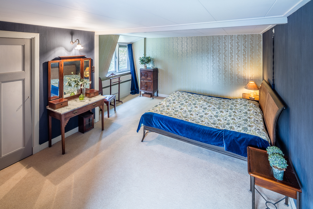 Grote slaapkamer aan de achterzijde met 2 raampartijen, ingebouwde kast en ruimte voor meerdere kasten