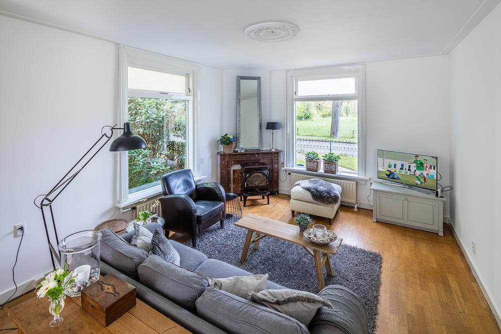 Zitgedeelte woonkamer met houtkachel en vrij uitzicht