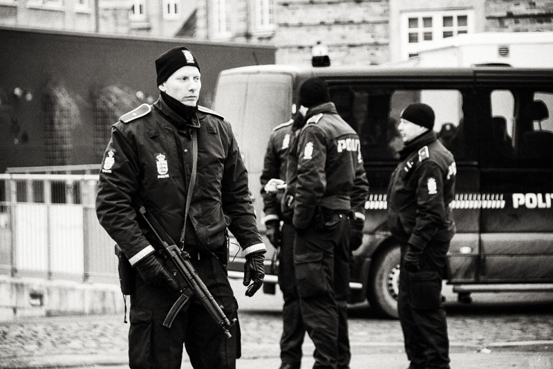 "Sunday, February 15th 2015 (morning) - Heavy armed police officers stand guard by the Culture Center ""Krudttønden"" (""Powder Keg"") where the documentary filmmaker, Finn Nørgaard, was killed."