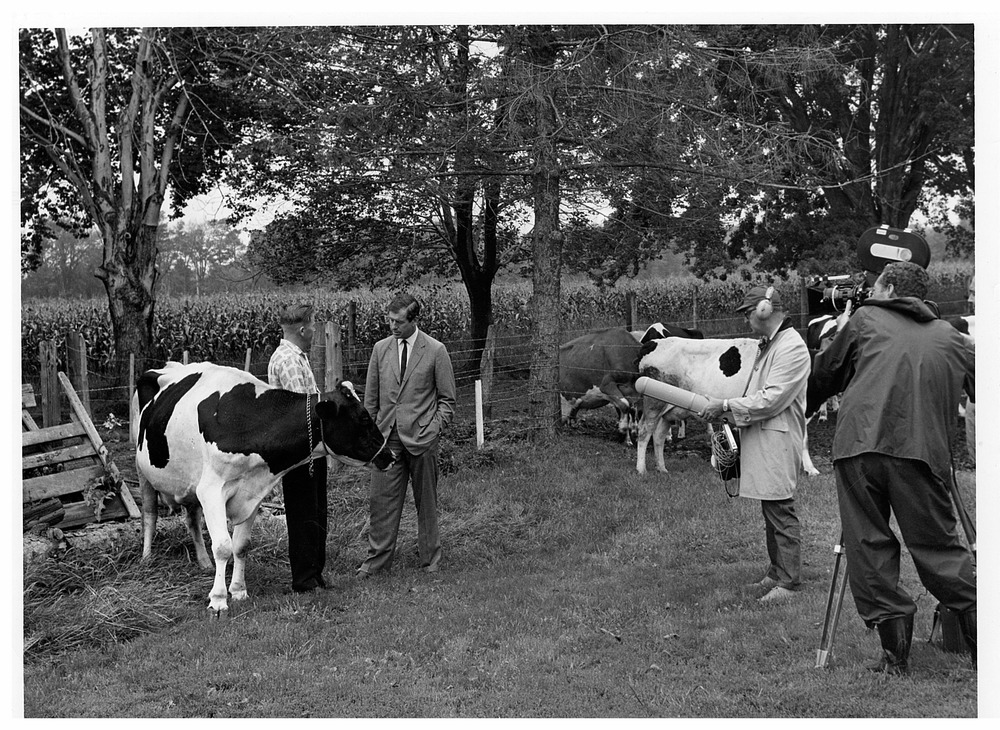 CBC broadcaster Stanley Burke (grey suit) interviewing a farmer during the filming of  The Air of Death . Photo courtesy of Pollution Probe.