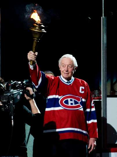 Jean Belliveau holding the torch at the Bell Centre.