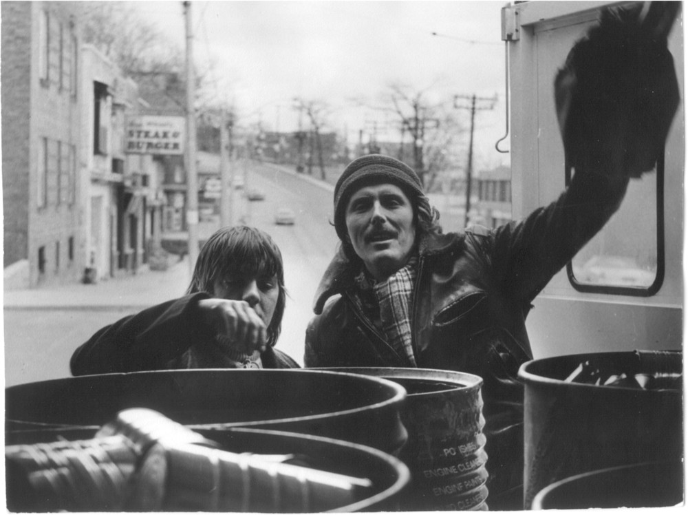 This photograph from the early 1970s features two unidentified members of the Is Five Foundation engaged in one of Canada's earliest roadside multi-material recycling programs. Note the barrels utilized for separating materials.