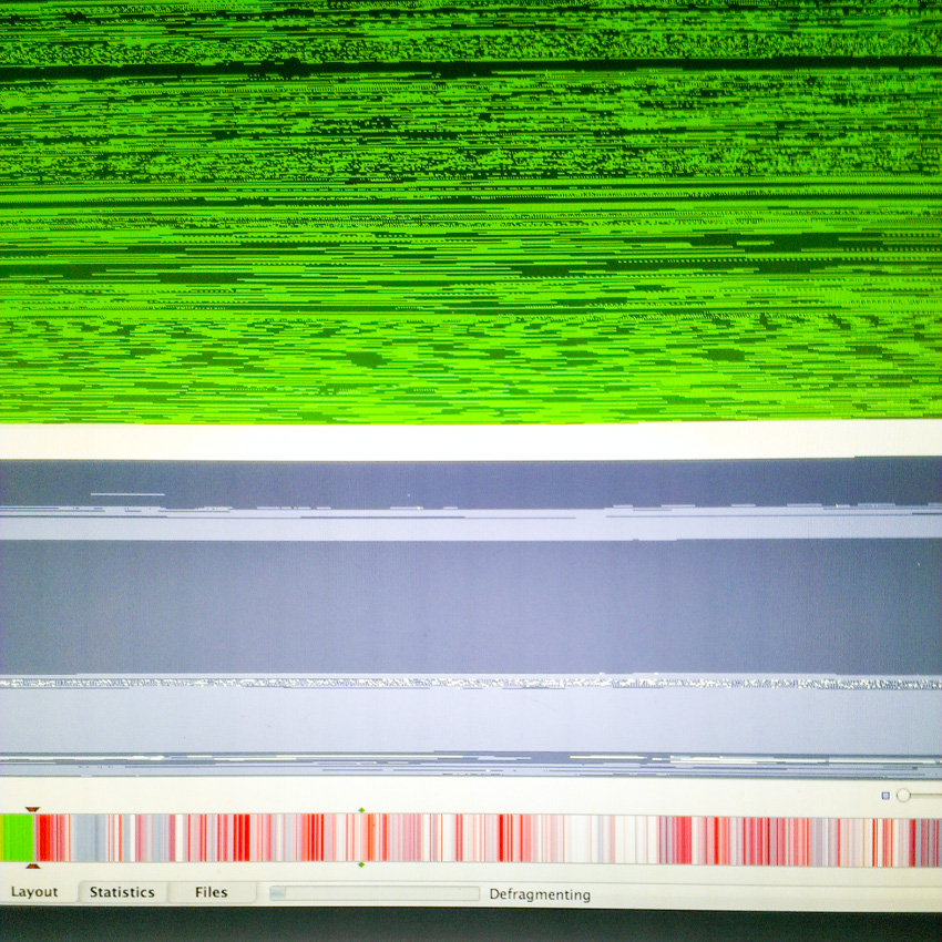 This is the iDefrag layout view of my early 2008 MacBook Pro's hard drive blocks just as I started the defragmentation process. The horizontal strip near the bottom, with red stripes in it, is a single look at the entire drive. Red stripes indicate fragmented files across the drive.