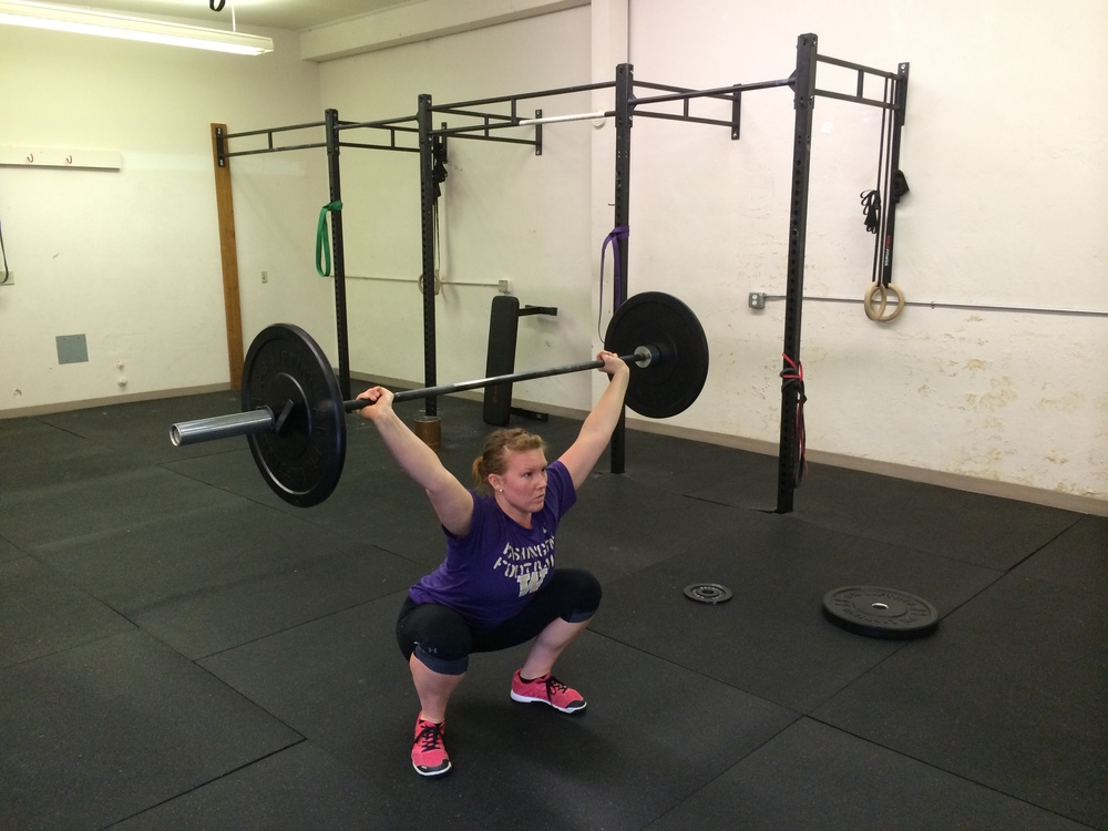 """squat-snatch"" receiving the barbell in a full squat. The squat snatch, squat clean, power snatch and power clean all end when you've fully stood up."