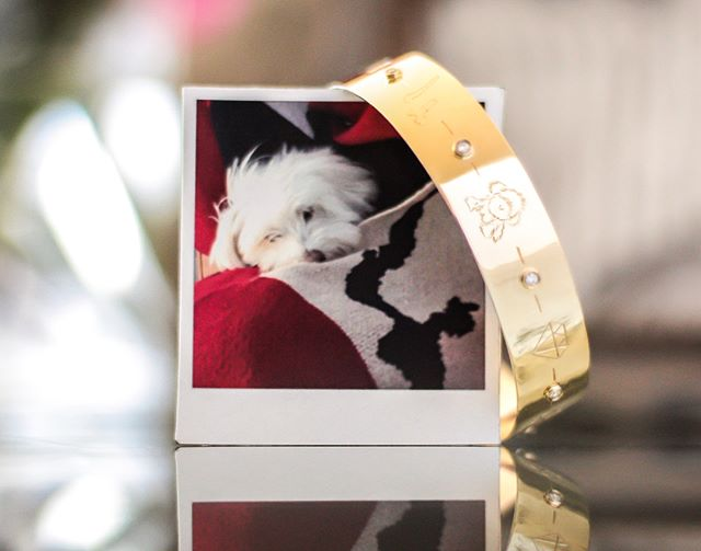 """A few weeks ago we said goodbye to my dog, Zoey, and it completely broke my heart. The next day, my new Life Bangle happened to be ready from the engraver. Featuring hand-engraved images that I picked to represent my life, with a little Zoey dog right in the middle, it could not have come at a better time! It makes me so happy to have a little reminder of her still """"following me around"""" everyday.  What images would put on yours?? Follow the link in bio to see what else I chose for mine and why!"""
