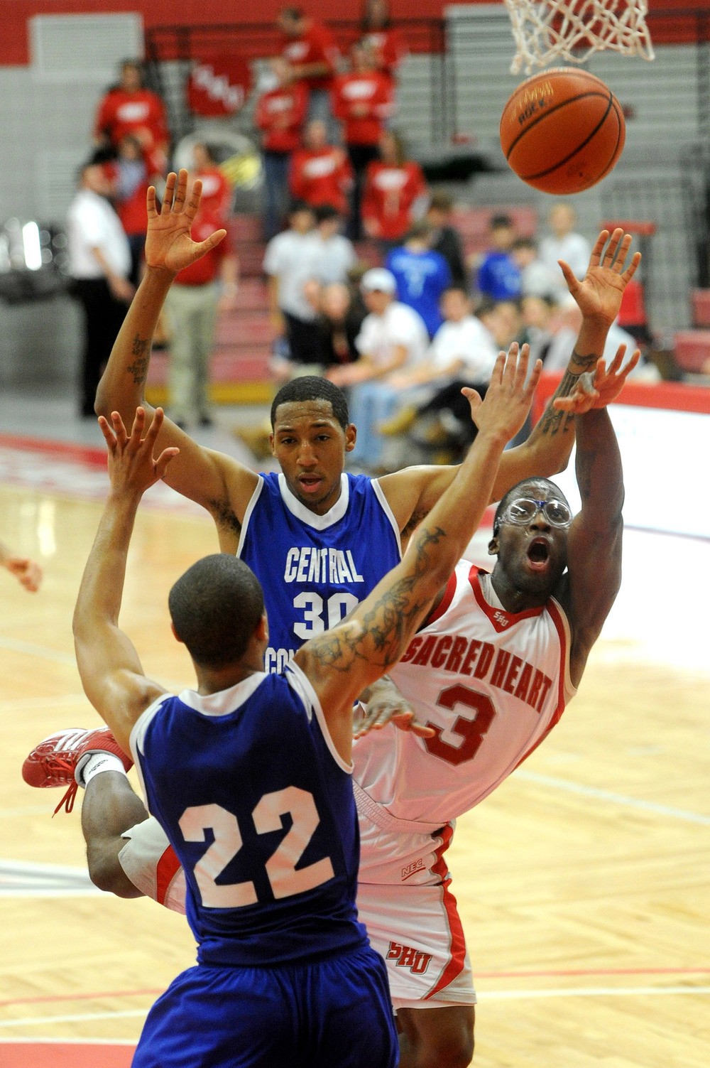 Sacred Heart University's Jerrell Thompson puts up a shot as he is defended by Ken Horton, back, and Devan Bailey, front, at CCSU in Fairfield on January 13, 2011.